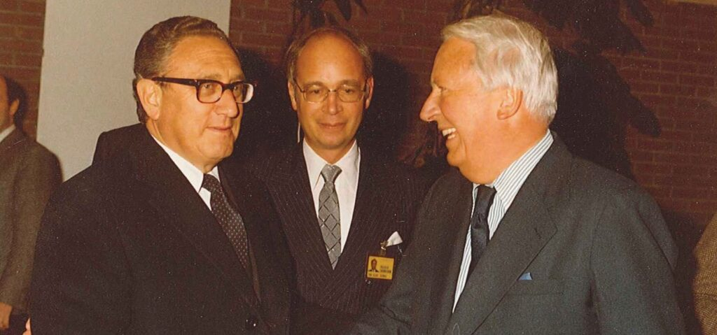 Henry Kissinger und sein ehemaliger Schüler, Klaus Schwab, begrüßen den ehemaligen britischen Premierminister Ted Heath auf dem WEF-Jahrestreffen 1980